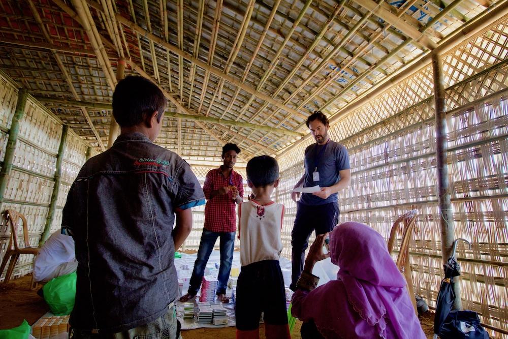 Rohingya interpreter works with doctor explaining medication dosage instructions medical facility Cox's Bazar Bangladesh Kutupalong camp